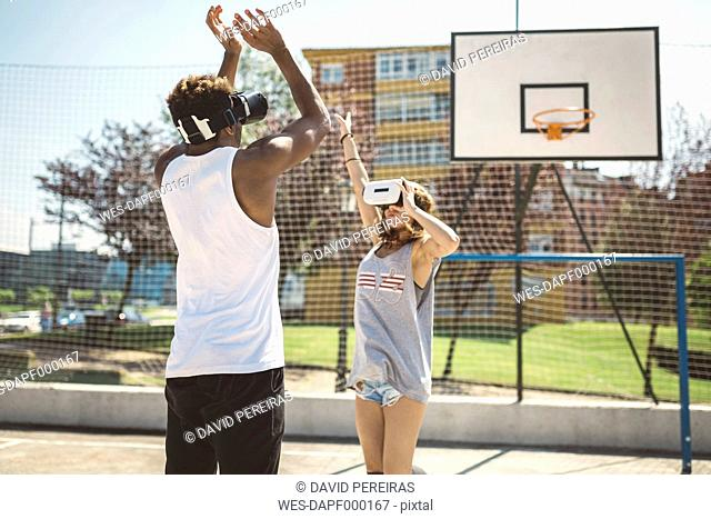 Young couple playing basketball with virtual reality glasses on