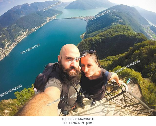 High angle view of mid adult couple taking selfie above Lake Lugano, Switzerland