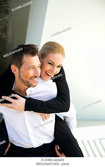 Portrait of happy businessman carrying woman piggyback