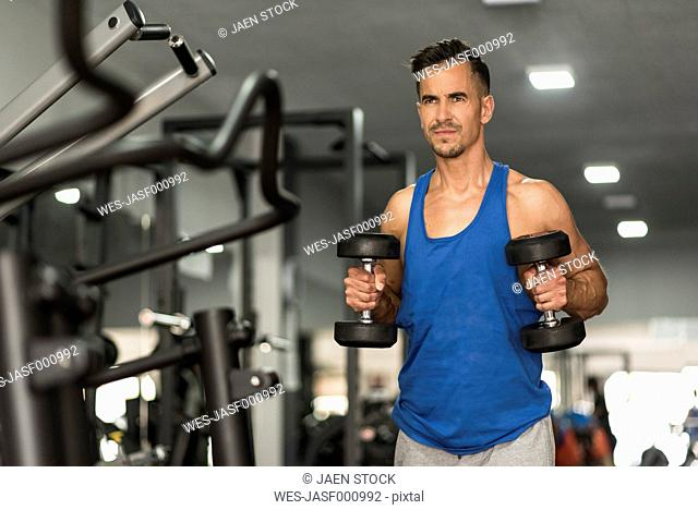 Man lifting dumbbells in gym