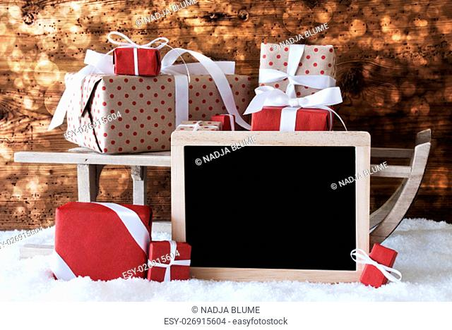 Sled With Christmas And Winter Decoration. Gifts And Presents On Snow With Wooden Background And Bokeh Effect. Chalkboard With Copy Space For Advertisement