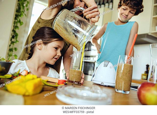 Mother with two children pouring a smoothie into glasses