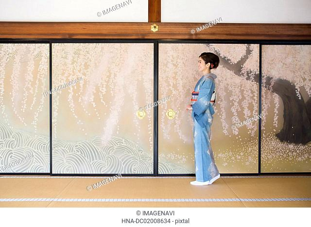 Young Japanese woman in kimono standing in front of Fusuma (Japanese traditional partition from paper)