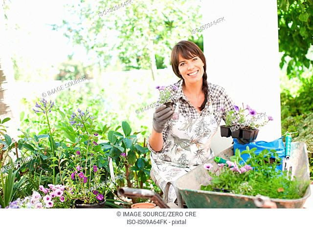 Woman potting plants outdoors