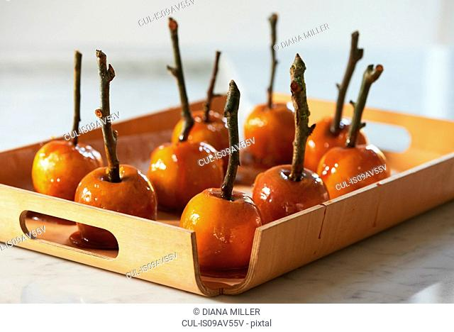 Toffee apples on sticks hardening on wooden tray