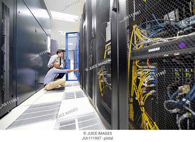 Technicians with laptop and digital tablet checking server in data centre hall