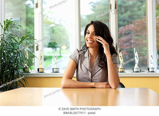 Hispanic woman talking on cell phone in dining room