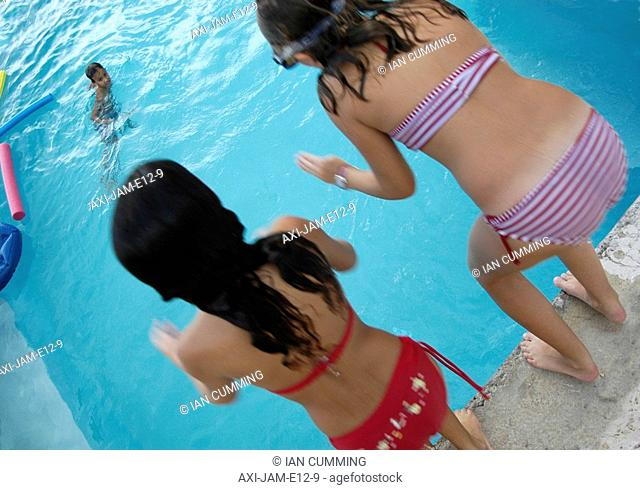 Two girls jumping into swimming pool, Jamaica