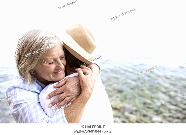 Happy senior couple hugging in front of the sea