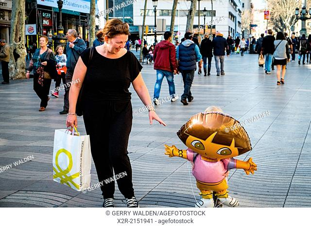 Small child totally hidden by Dora the Explorer ballon whilst walking with mother (La Rambla, Barcelona)