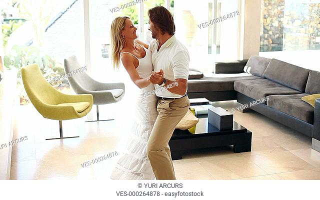 Happy couple dancing together playfully in their living room