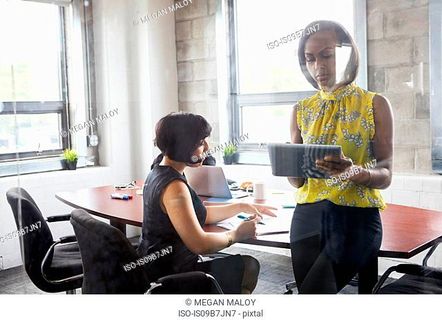 Two women working together in meeting room, brainstorming, using digital tablet