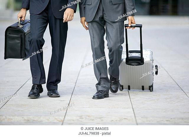 Two businessmen walking with suitcases