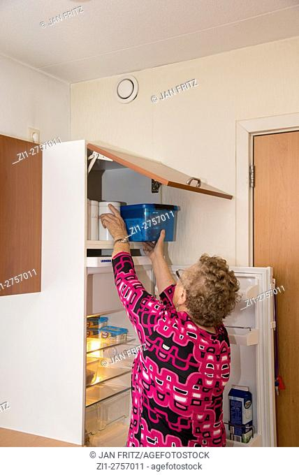 old woman in home for the aged reaching for goods in cupboard in kitchen