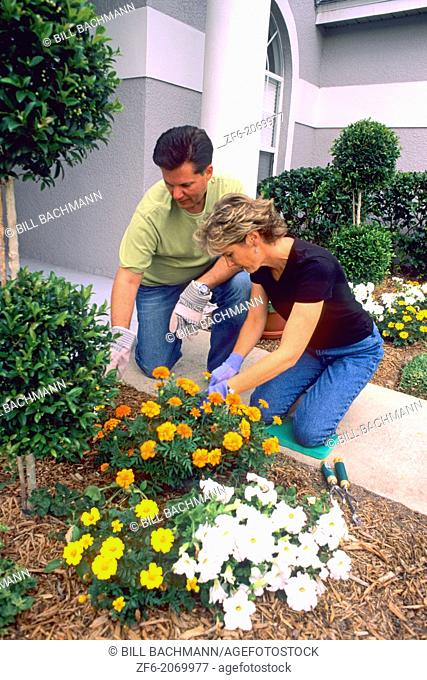 Married Couple at Home Planting Flowers in Front of House