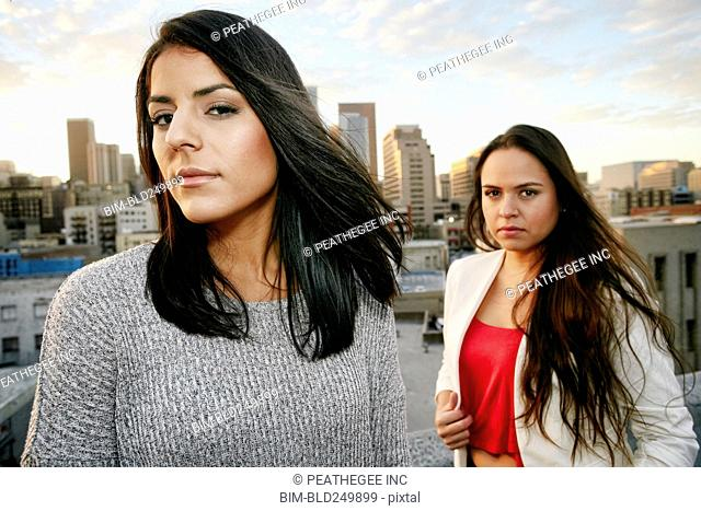Portrait of serious Hispanic women on urban rooftop at sunset
