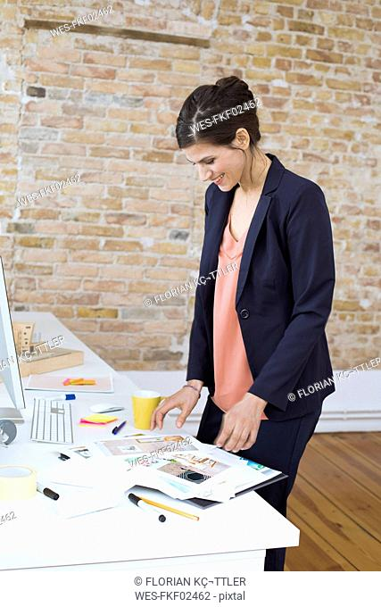 Smiling businesswoman looking at photos at desk in office