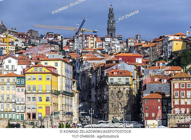 Row of buildings on the Douro riverfront in Porto city, Portugal. View with bell tower of Clerigos Church