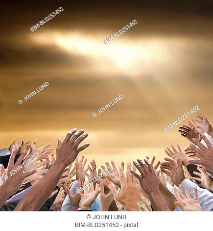 Hands of crowd reaching to sky