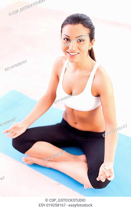 Taking stress away. Top view of attractive young Indian woman sitting in lotus position and smiling at camera