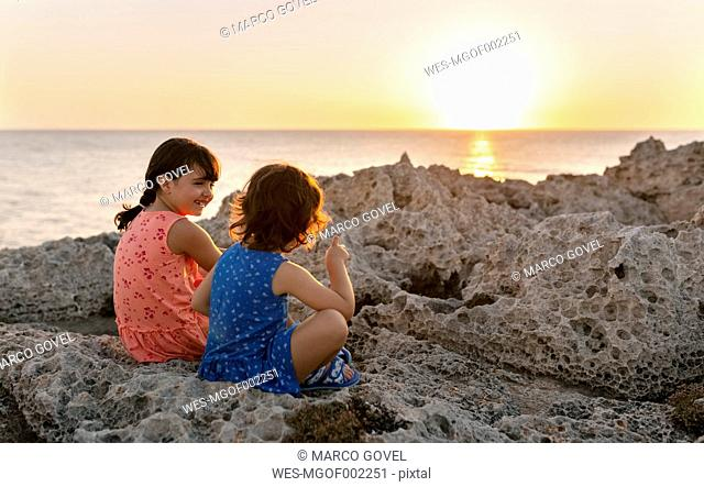 Back view of two little sisters sitting at rocky coast by sunset