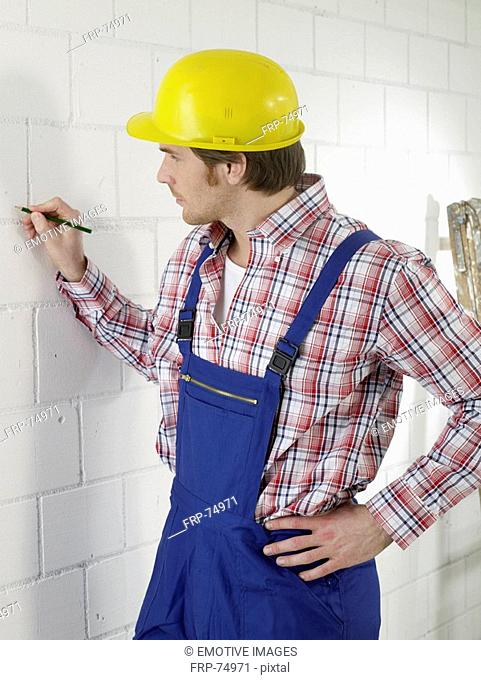 Construction worker is marking with a pencil on the wall