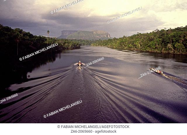 Aerial view of tourist boats going up Carrao river showing tepuis in the bakground. Canaima National Park, Bolivar State, Southern Venezuela