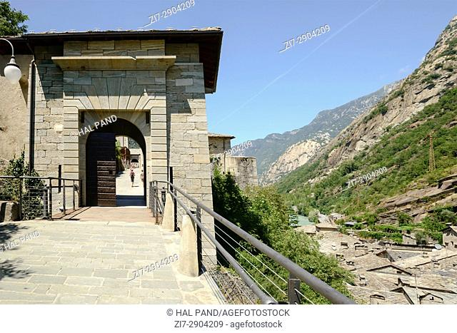 view of fortification entrance at medieval mountain village set in a narrow valley, shot on a bright summer day at Bard, Aosta valley, Italy