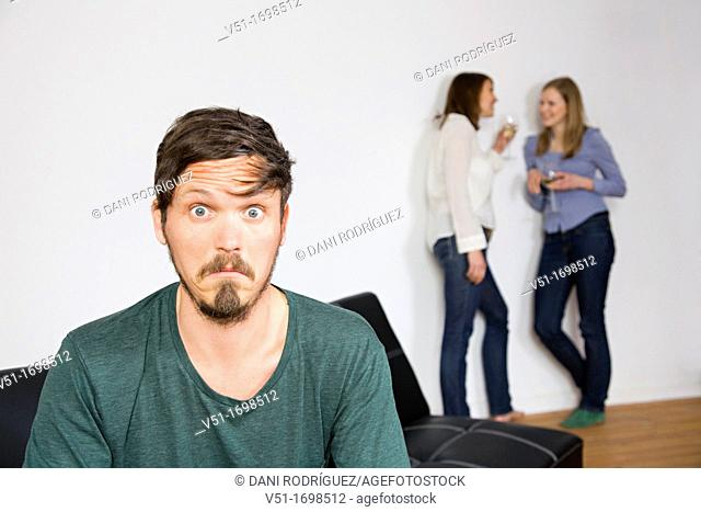 Confused man, and two women talking in background