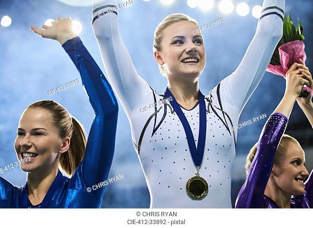 Female gymnasts celebrating victory waving on winners podium
