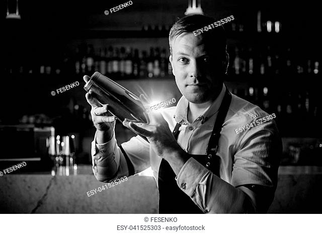Black and white photo of barman making an alcoholic cocktail using a shaker on the background of shelves with bottles