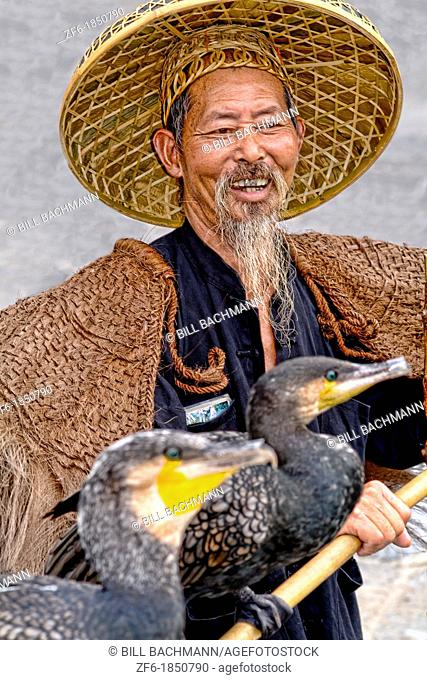 Old man fisherman with his cormorant fishing bird in traditional costume in Yangshuo China
