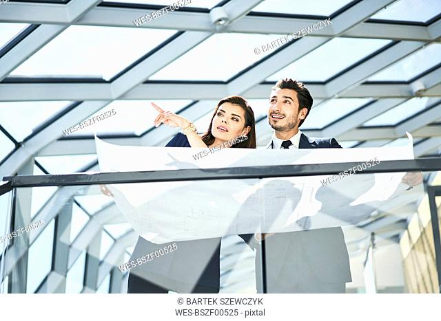 Businesswoman and businessman with plan talking in office