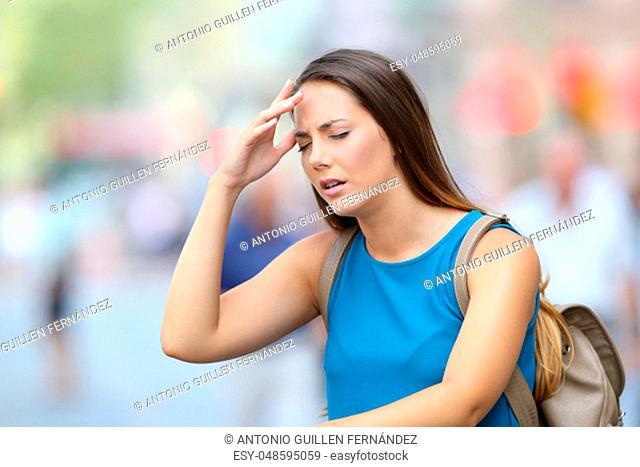 Single woman suffering headache outdoors in the street