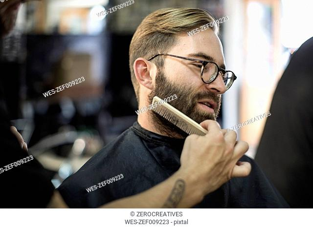 Barber combs beard of customer