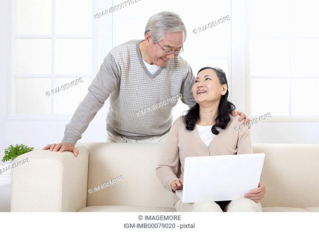 Senior couple holding laptop and smiling happily