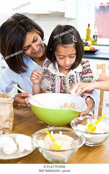 Mother baking with daughter in kitchen