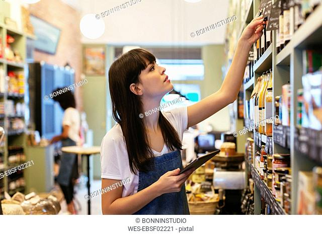 Woman with tablet at shelf in a store