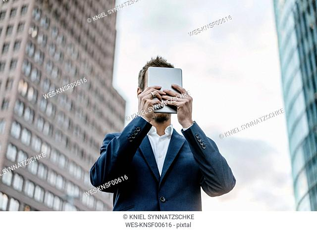 Germany, Berlin, businessman hiding his face behind mini tablet