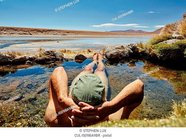 Man relaxing in water pool, rear view, Salar de Chiguana, Chiguana, Potosi, Bolivia, South America