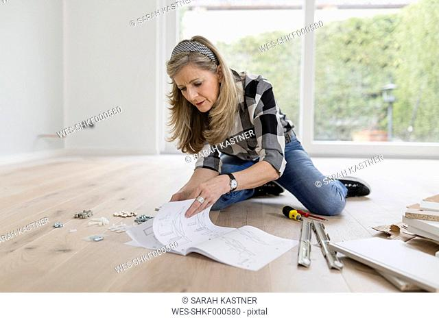 Woman crouching on the floor of an empty room reading instructions