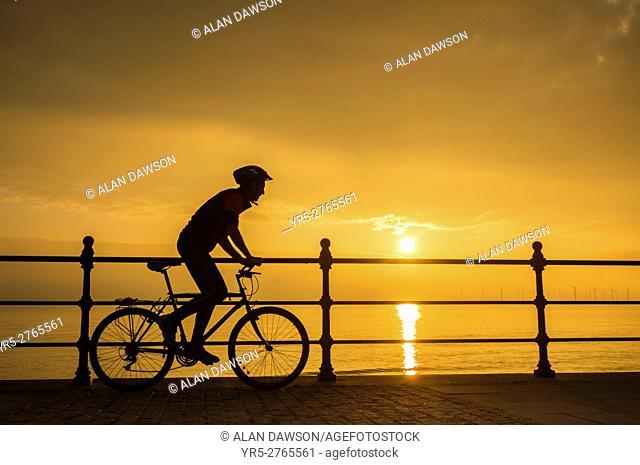 Seaton Carew, north east England, United Kingdom. A mountain biker at Seaton Carew on the north east coast as the sun rises over the North sea