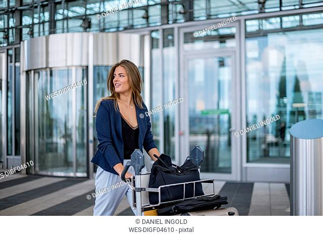 Smiling young woman pushing luggage trolley looking around