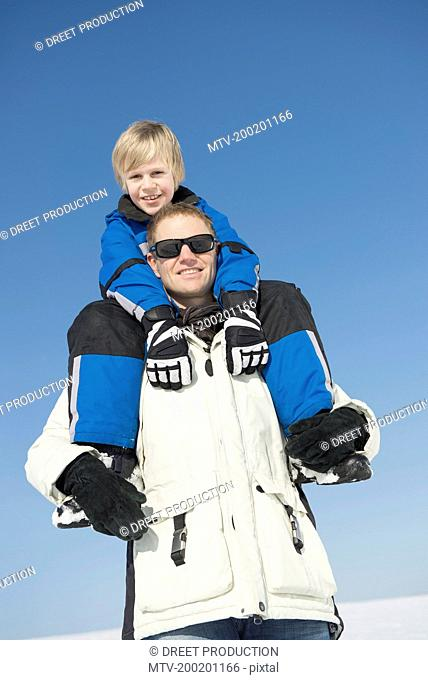 Father carrying son on shoulder, smiling, Bavaria, Germany