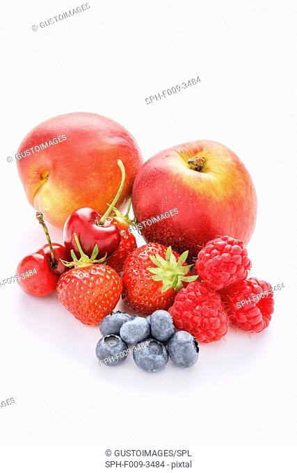 A selection of mixed fruit on a white background. These include, cherries, nectarines, strawberries, plums, blueberries and raspberries