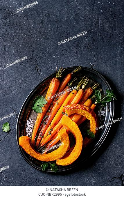 Roasted young whole carrot and sliced pumpkin with greens and sea salt. Served on vintage metal tray over black texture background