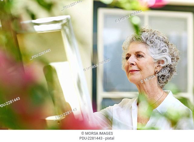 Senior woman painting on canvas at porch
