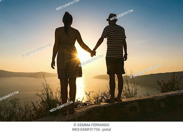 Greece, Santorini, Fira, couple holding hands and enjoying sunset over the Santorini caldera