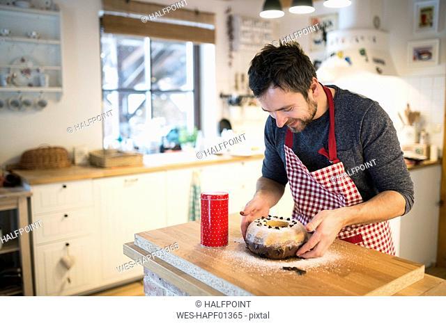 Man standing in kitchen garnishing ring cake