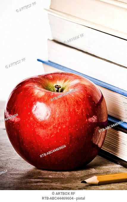 Close-up of an apple near a stack of books